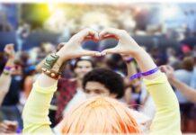 En person håller upp sina händer för att göra ett hjärta i en samling av människor.